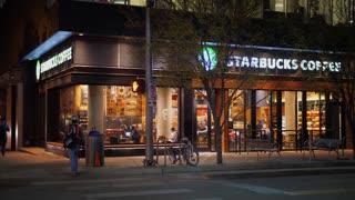 AUSTIN, TX - Circa December, 2017 - A nighttime establishing shot of a Starbucks Coffee Shop on Lavaca Street in downtown Austin, Texas.