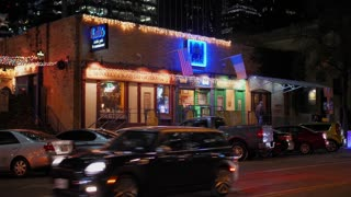 AUSTIN, TX - Circa December, 2017 - A nighttime establishing shot of bars and restaurants on West 4th Street in downtown Austin, Texas. Day/night matching available.