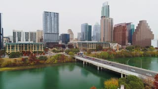 AUSTIN, TX - Circa December, 2017 - A slow forward aerial establishing shot of Austin, Texas and the Colorado River on an overcast day as traffic flows over the S 1st Street Bridge.