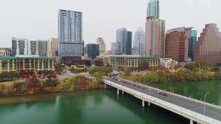 AUSTIN, TX - Circa December, 2017 - A slow rising reverse aerial establishing shot of Austin, Texas and the Colorado River on an overcast day as traffic flows over the S 1st Street Bridge.