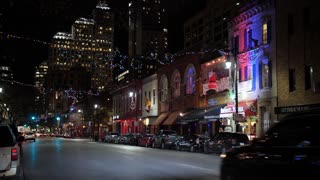 AUSTIN, TX - Circa December, 2017 - Traffic passes bars and restaurants decorated for Christmas on E 6th Street in Austin's historic tourist district.