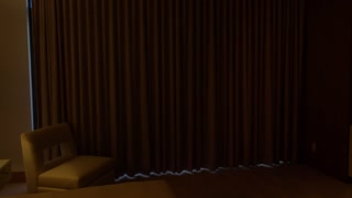 Automatic drapes open in an upscale bedroom or hotel room to reveal a large fish tank. Abstract.
