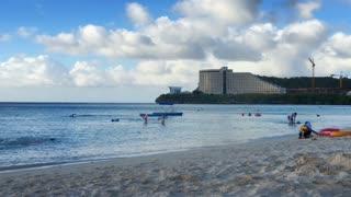 Beachgoers play on a tropical resort beach.