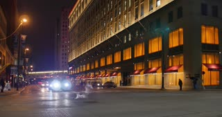 CLEVELAND - Circa March, 2017 - A night time establishing shot of traffic passing by JACK Casino in the Higbee Building in downtown Cleveland.
