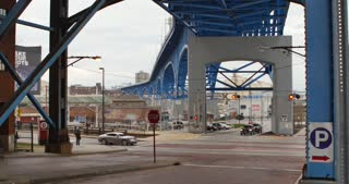 CLEVELAND, OH - Circa April, 2017 - An overcast daytime establishing shot of pedestrians, traffic, and trains under the Main Avenue Bridge, part of the Cleveland Memorial Shoreway.
