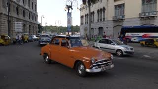 HAVANA, CUBA - Circa July, 2017 - A daytime establishing shot of vintage classic cars traveling on the streets of Havana, Cuba.
