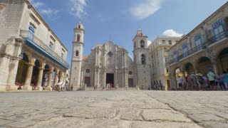 HAVANA, CUBA - Circa July, 2017 - A low angle daytime establishing shot of tourists visiting Cathedral Plaza Square in the old town district of Havana.