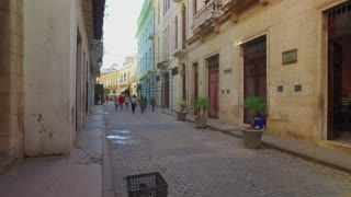 HAVANA, CUBA - Circa July, 2017 - A tracking POV dolly establishing shot walking in the narrow streets in Havana's old town historic district.