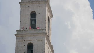 HAVANA, CUBA - Circa July, 2017 - Tourists enjoy the view from atop the tower of Basilica Menor de San Francisco de Asis in the old town district of Havana. Shot at 48fps.