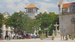 HAVANA, CUBA - Circa July, 2017 - Wide establishing shot of tourists visiting the town square outside Convento de San Francisco de Asis in the old town district of Havana, Cuba. Shot at 48fps.