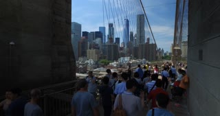 NEW YORK - Circa June, 2017 - A high angle personal perspective walking over the Brooklyn Bridge though the crowds of tourists on a sunny summer day.
