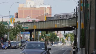 NEW YORK CITY - Circa June, 2017 - A daytime establishing shot of busy Queens Boulevard as an elevated subway train travels above in the distance.
