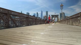 NEW YORK CITY - Circa June, 2017 - A dramatic low to high dolly up shot of pedestrians and tourists walking on the Brooklyn Bridge on a hot summer day.