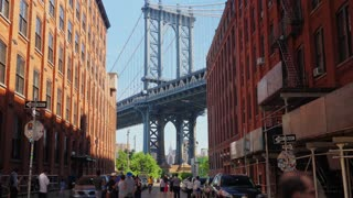 NEW YORK CITY - Circa June, 2018 - A daytime view of tourists standing on Washington Street looking at the icon Manhattan Bridge.