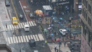 NEW YORK CITY - Circa October, 2017 - A high angle realtime view of traffic and pedestrians with umbrellas on the streets of Manhattan.