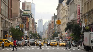 NEW YORK CITY - Circa October, 2017 - A slow motion middle of the street view of pedestrians in a Manhattan 6th Avenue crosswalk with the Freedom Tower in the distance.