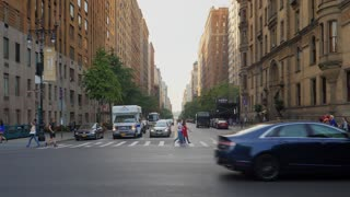 NEW YORK CITY - Circa October, 2017 - An early morning establishing shot of traffic and pedestrians on a typical midtown Manhattan street and crosswalk.