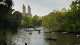 NEW YORK CITY - Circa October, 2017 - Boaters enjoy an early autumn evening on The Lake in Central Park with upscale apartment buildings seen in the distance.