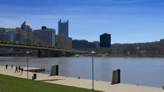 PITTSBURGH, PA - Circa April, 2017 - A daytime panning establishing shot of the Pittsburgh city skyline as people walk and run on the North Shore.