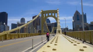 PITTSBURGH, PA - Circa April, 2017 - A slowly moving dolly establishing shot of people and traffic passing over the Roberto Clemente Bridge over the Allegheny River.