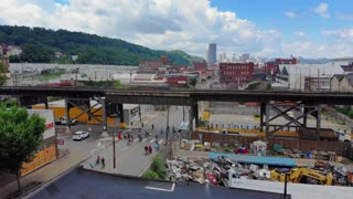 PITTSBURGH, PA - Circa June, 2018 - A slow reverse aerial establishing shot of the Lawrenceville during Open Streets, a Pittsburgh neighborhood experiencing the benefits of gentrification.