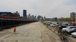 PITTSBURGH, PA - Circa May, 2018 - A forward aerial establishing shot of the Pittsburgh skyline as a bicyclist rides past the loading docks in the Strip District.