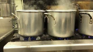 Pots boiling pierogies in an industrial kitchen.