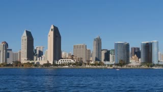 SAN DIEGO, CA - Circa February, 2017 - A daytime establishing shot of the San Diego skyline as seen from Coronado Island shoreline as boaters pass by in the bay.