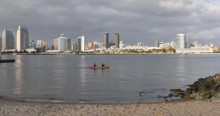 SAN DIEGO, CA - Circa February, 2017 - A daytime establishing shot of the San Diego skyline as seen from Coronado Island shoreline as kayakers pass by.