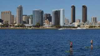 SAN DIEGO, CA - Circa February, 2017 - Two guys on stand up paddle boards pass by on San Diego Bay on a sunny day.
