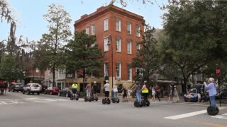 SAVANNAH, GA - Circa February, 2018 - A daytime exterior establishing shot of a typical street corner in downtown Savannah, Georgia as tourists on Segway scooters pass by.