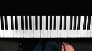 The public domain song, Happy Birthday To You, is played on an electric piano. Overhead shot, with audio.