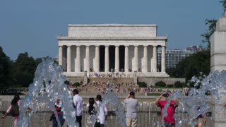 WASHINGTON, D.C. - Circa August, 2017 - A sunny daytime shot of tourists visiting the World War II Memorial with the Lincoln Memorial in the distance. Shot at 48fps.