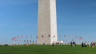 WASHINGTON, D.C. - Circa August, 2017 - A wide slow motion establishing shot of tourists visiting the base of the Washington Monument. Shot at 48fps.