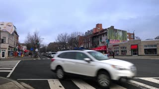 WASHINGTON DC - Circa March, 2018 - An overcast establishing shot of traffic passing businesses in the Woodley Park, Mt. Pleasant area of Washington, DC on a late winter day.
