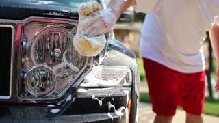 Man Washes Car Day outside Summer Headlight