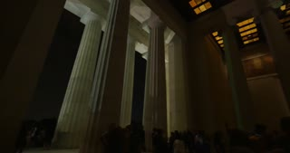 WASHINGTON, D.C. - Circa July, 2015 - A nighttime interior establishing shot of the Lincoln Memorial as tourists view the statue of a sitting Abraham Lincoln.