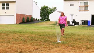 Woman Moves Home Lawn Sprinkler