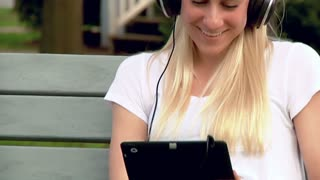 Young Woman Listens to Music in the Park with Headphones and iPad