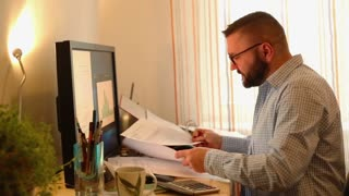 Angry businessman with documents by desk in the office home