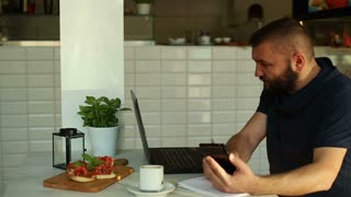 Angry man with cellphone in front of computer in restaurant