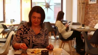 Angry, unhappy woman talking on cellphone in cafe