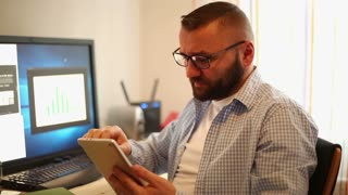 Attractive businessman working with tablet computer in office home
