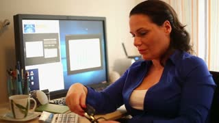 Attractive woman working on the computer in office and smiles to camera