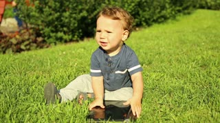 Baby is playing with laptop on the grass
