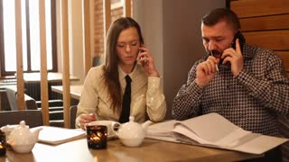 Business couple working with smartphone and documents sitting in cafe