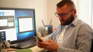 Businessman using smartphone by desk in office home