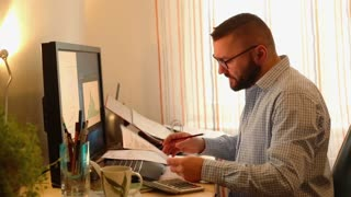 Businessman writing notes in documents sitting by table at home