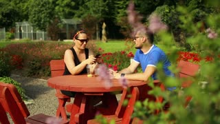 Couple is talking at the table in the park