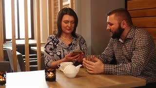 Couple sitting in the restaurant and looking on mobile phone drink beer